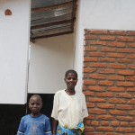Eda Saopa and her son in front of their new home